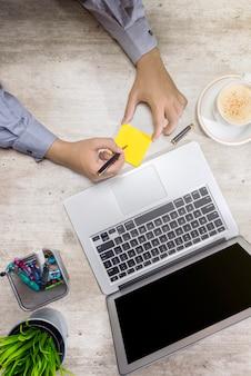 Vue de dessus d'homme d'affaires écrivant dans des notes autocollantes avec ordinateur portable, café, plante en pot et accessoires