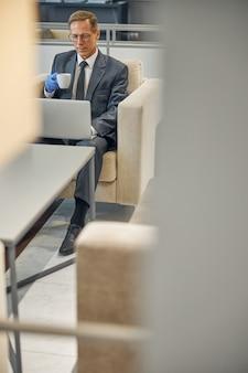 Vue de dessus d'un homme d'affaires mature qui perd du temps avant le vol avec un ordinateur portable et une tasse de boisson chaude