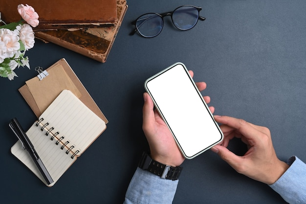 Vue de dessus de l'homme d'affaires tenant une maquette de téléphone intelligent avec écran vide sur une surface bleu foncé