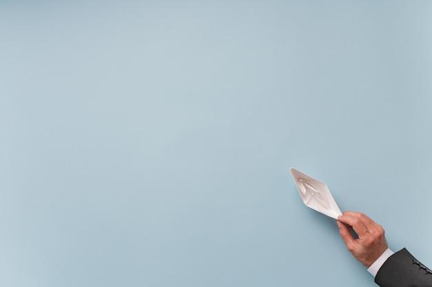Vue de dessus de l'homme d'affaires tenant le papier fait bateau origami sur bleu