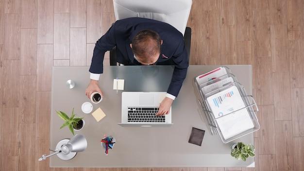 Vue de dessus d'un homme d'affaires tenant une tasse de café tout en tapant les statistiques de l'entreprise