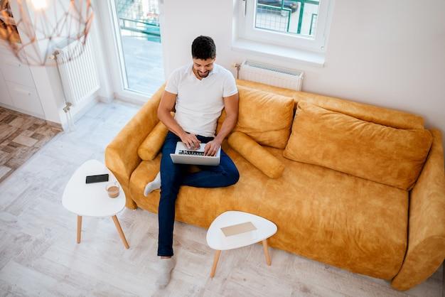 Vue de dessus d'un homme afro-américain assis sur un canapé avec ordinateur portable.
