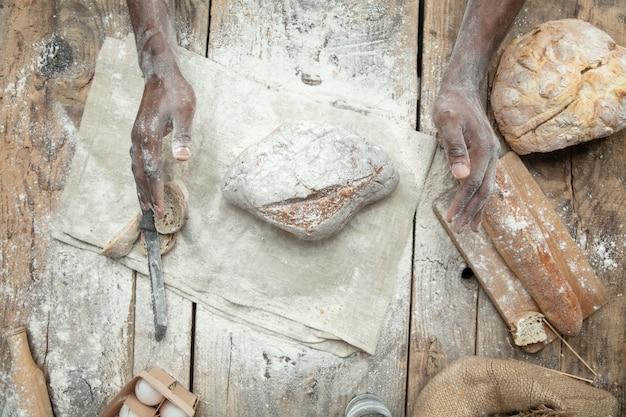 Vue de dessus de l'homme afro-américain cuisine des céréales fraîches, du pain, du son sur une table en bois