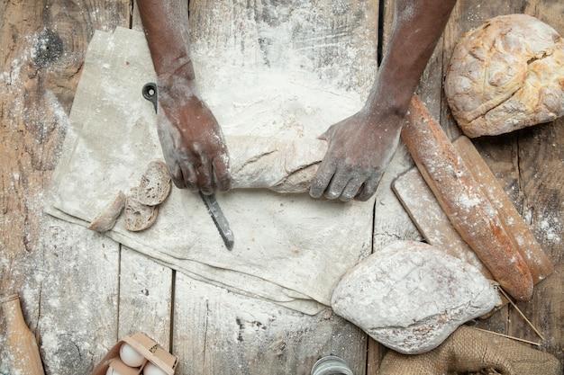 Vue de dessus de l'homme afro-américain cuit des céréales fraîches, du pain, du son sur une table en bois. manger savoureux, nutrition, produit artisanal. nourriture sans gluten, mode de vie sain, fabrication biologique et sûre. fait main.