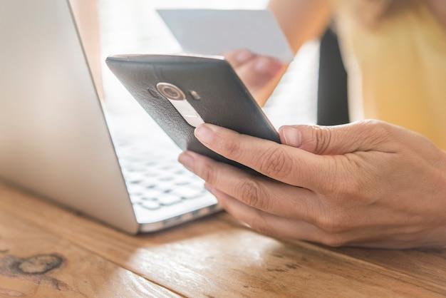 Vue de dessus de l'homme à l'aide d'une carte de crédit pour les achats en ligne