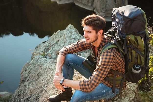 Vue de dessus de l'homme d'aventure assis sur un rocher à la recherche de suite