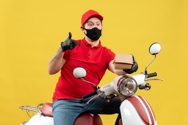 Vue de dessus de l'homme de courrier émotionnel surpris portant chemisier rouge et gants de chapeau en masque médical assis sur ordre de maintien de scooter