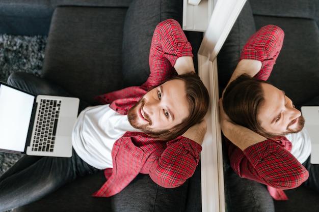 Vue de dessus d'un homme détendu heureux utilisant un ordinateur portable à la maison