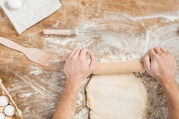 Vue de dessus de l'homme faisant la pâte à pizza