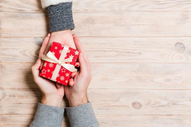Vue de dessus d'un homme et une femme se félicitant avec un cadeau sur bois.