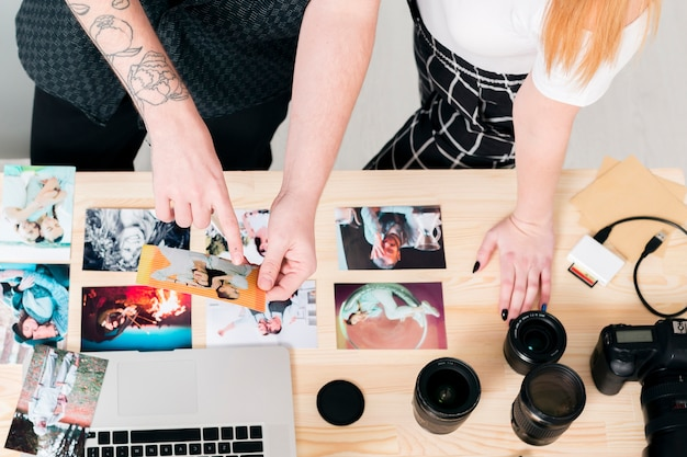 Vue de dessus homme et femme travaillant avec des photos et un ordinateur portable