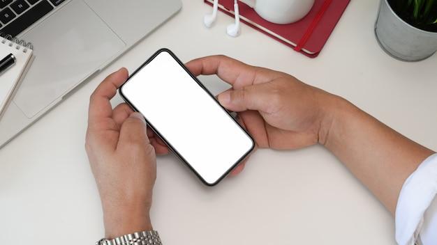 Vue de dessus l'homme mains tenant smartphone smartphone écran blanc sur l'espace de travail