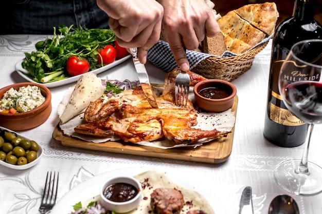 Vue de dessus un homme mangeant du tabac sur du pain pita avec sauce et oignons verts et tomates