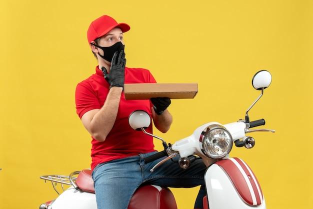 Vue de dessus de l'homme de messagerie choqué portant chemisier rouge et gants de chapeau en masque médical assis sur ordre de maintien de scooter