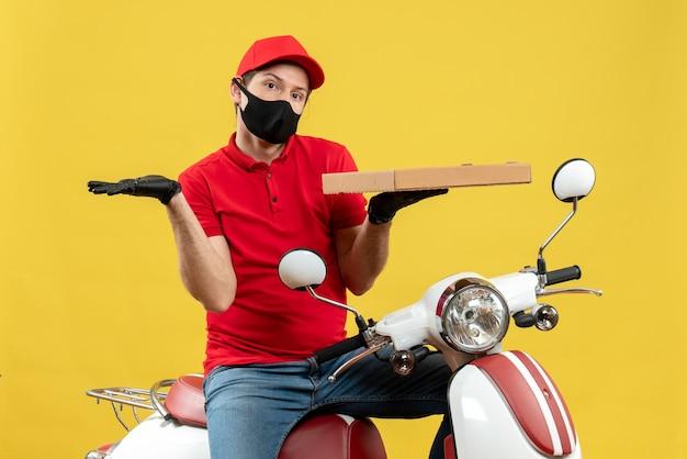 Vue de dessus de l'homme de messagerie confus portant chemisier rouge et gants de chapeau dans l'ordre de maintien de masque médical montrant quelque chose sur le côté gauche