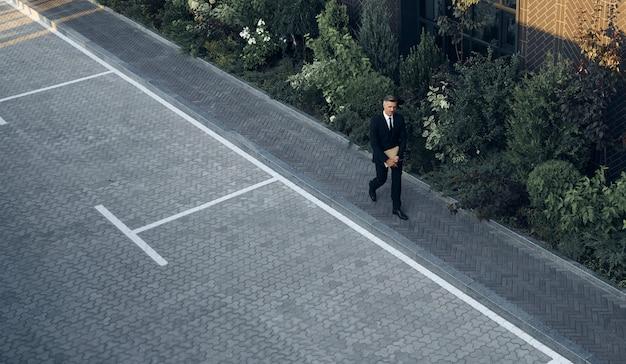 Vue de dessus d'un homme mûr en costume complet portant un ordinateur portable tout en marchant à l'extérieur