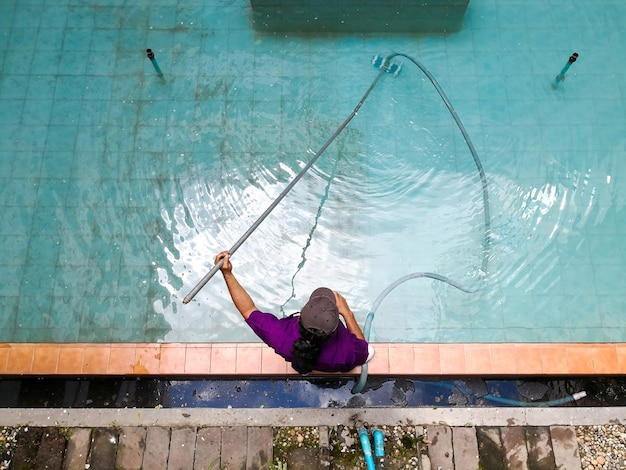 Vue de dessus de l'homme nettoyant la piscine avec un aspirateur à tube.