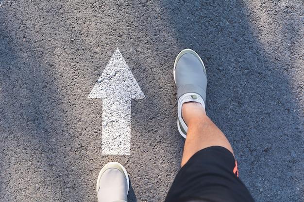 Vue de dessus d'un homme portant des chaussures blanches en choisissant un chemin marqué par des flèches blanches.