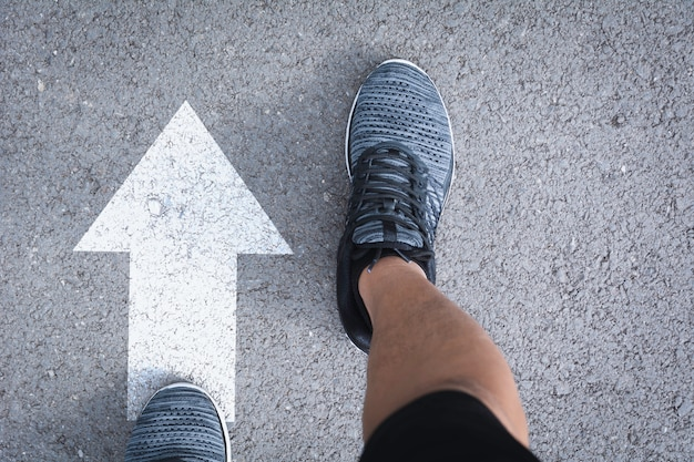 Vue de dessus d'un homme portant des chaussures en choisissant un chemin marqué par des flèches blanches.