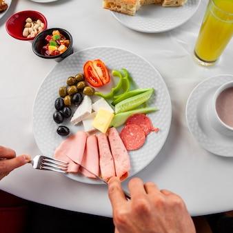 Vue de dessus l'homme prenant son petit déjeuner manger des saucisses.