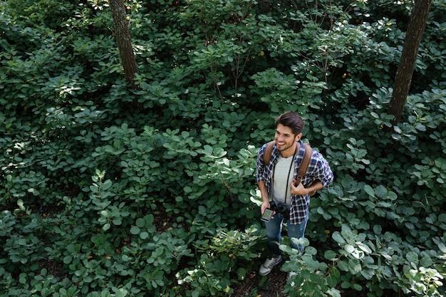 Vue de dessus de l'homme souriant en forêt