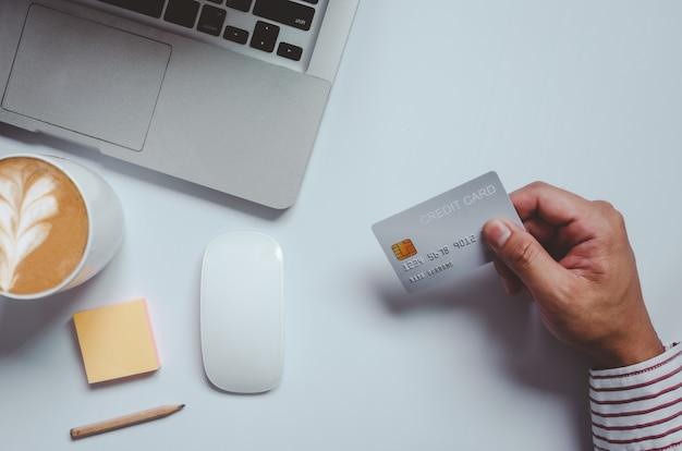 Vue de dessus homme tenant une carte de crédit et sur le bureau. bloc-notes et stylo ordinateur portable