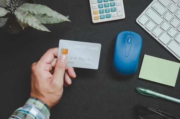 Vue de dessus homme tenant une carte de crédit et sur le bureau