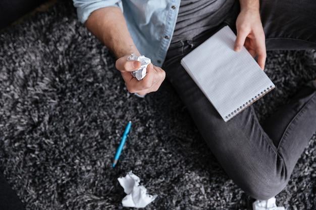 Vue de dessus d'un homme tenant du papier froissé et un bloc-notes assis sur un tapis