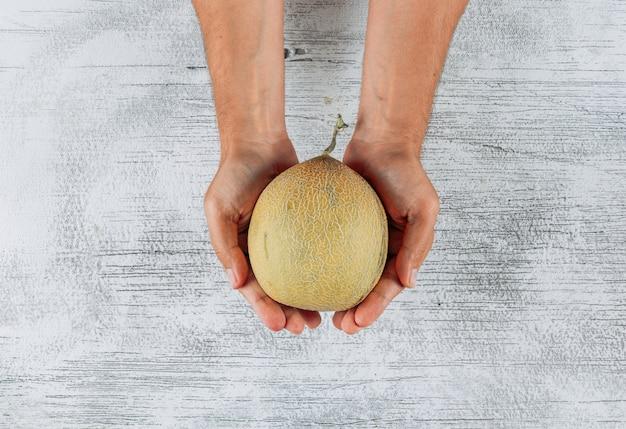 Vue de dessus homme tenant melon sur fond en bois clair. horizontal