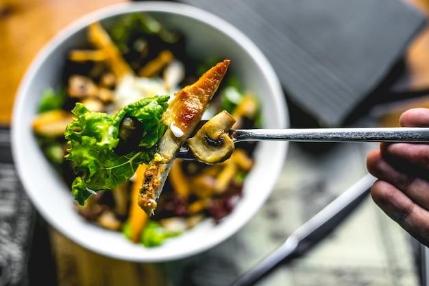 Vue de dessus un homme tient une fourchette avec salade de poulet frit et champignons