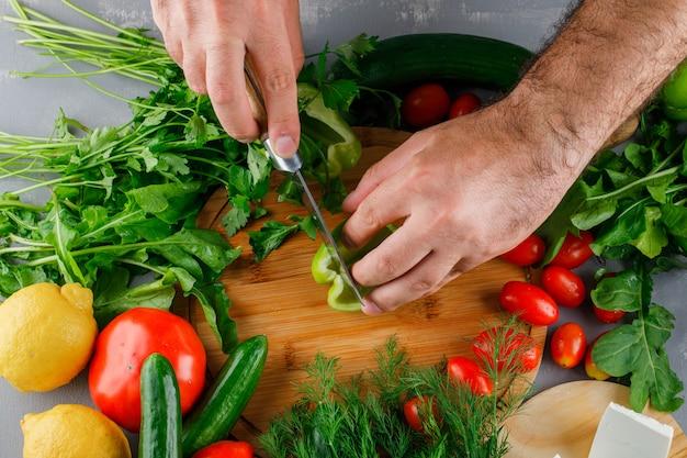 Vue de dessus homme trancher le poivre vert sur une planche à découper avec des tomates, du sel, du fromage, du citron sur une surface grise