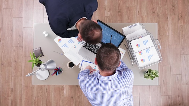 Vue de dessus des hommes d'affaires analysant les statistiques de gestion à l'aide d'un ordinateur portable