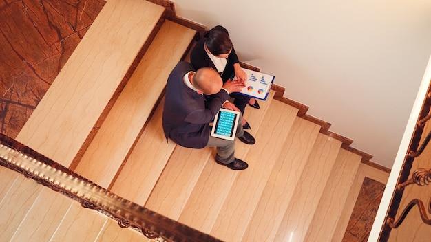 Vue de dessus des hommes d'affaires travaillant sur un projet de date limite pendant que des collègues passent à côté d'eux dans les escaliers. entrepreneur travaillant ensemble en soirée au travail d'entreprise expliquant le projet difficile.