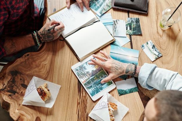 Vue de dessus des hommes assis à une table en bois et regardant de beaux endroits exotiques lors de la planification du voyage