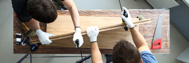 Vue de dessus des hommes charpentiers mettant un bloc de bois dans un étau. menuisiers utilisant des outils de menuiserie spéciaux pour l'assemblage des meubles. hommes travaillant avec planche de bois. concept d'atelier de menuiserie