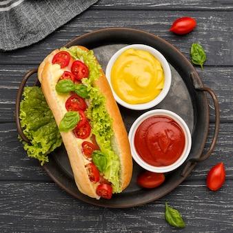 Vue de dessus hot dog avec bols de sauce