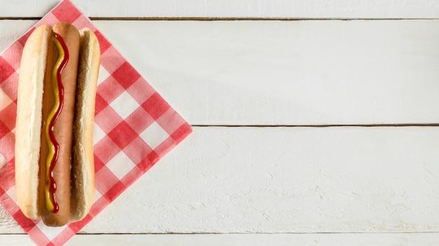 Vue de dessus hot-dog avec serviette sur fond de bois
