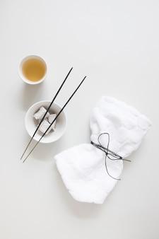 Vue de dessus de l'huile; bâtonnet d'encens; pierre ponce et serviette attachée sur fond blanc