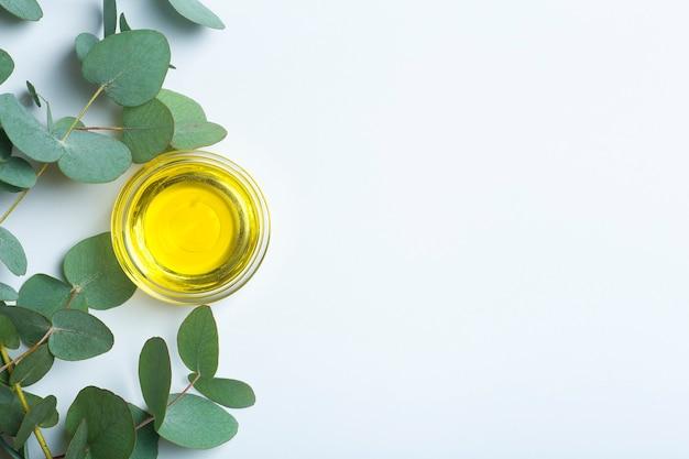 Vue de dessus de l'huile d'eucalyptus et des feuilles sur fond bleu clair