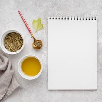 Vue de dessus huile, herbes et bloc-notes vierge
