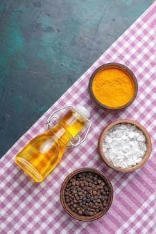 Vue de dessus de l'huile d'olive avec différents assaisonnements sur fond bleu foncé ingrédient produit alimentaire