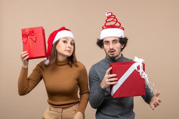 Vue de dessus de l'humeur du nouvel an et concept de fête - joli couple confus tenant des cadeaux portant des chapeaux de père noël sur fond gris