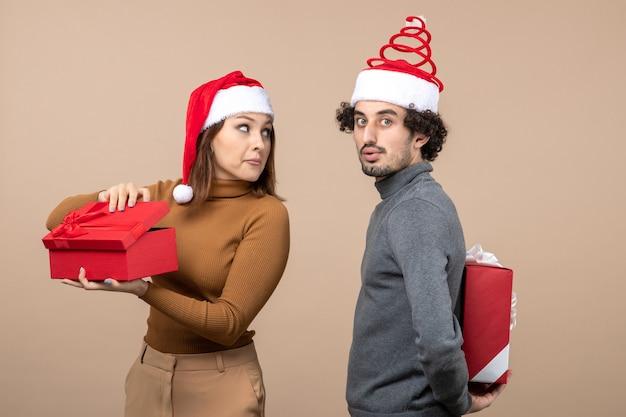 Vue de dessus de l'humeur du nouvel an et du concept de fête - surpris beau couple tenant des cadeaux portant des chapeaux de père noël