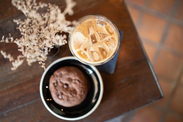 Vue de dessus de ice latte coffeein un verre avec cookie aux pépites de chocolat sur une table en bois