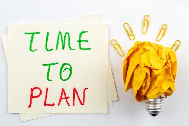 Vue de dessus idée ampoule concept avec papier froissé temps à planifier écrit sur papier sur table