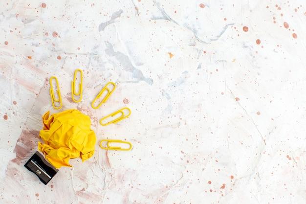 Vue de dessus idée ampoule concept avec papier jaune froissé pinces taille-crayon taille-crayon sur fond gris avec copie place