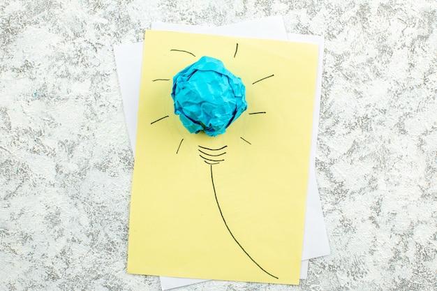 Vue de dessus idée ampoule concept sur papier jaune sur table