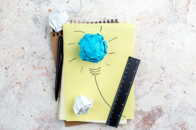Vue de dessus idée ampoule concept sur papier règle stylo papiers froissés sur table