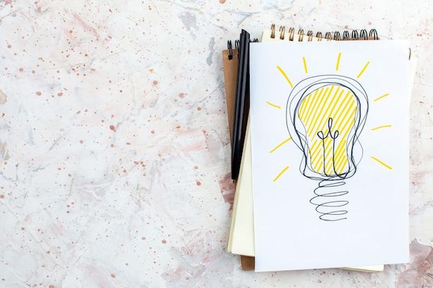 Vue de dessus idée ampoule dessin sur papier sur bloc-notes stylo sur table espace libre