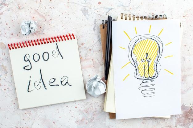Vue de dessus idée ampoule dessin sur papier bonne idée écrite sur bloc-notes stylo sur table